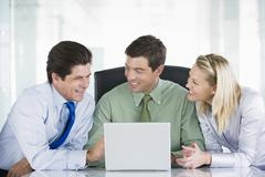 Three businesspeople in a boardroom looking at laptop smiling Stock Photos