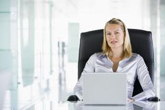 Businesswoman in office with a laptop - stock photo