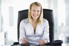 Businesswoman in office with personal organizer smiling - stock photo