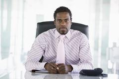 Businessman sitting in office with personal organizer Stock Photos