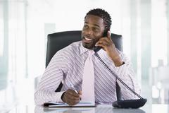 Businessman sitting in office with personal organizer open on telephone Stock Photos