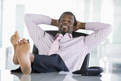 Businessman sitting in office with feet on desk relaxing and smiling - stock photo