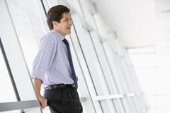 Businessman standing in corridor laughing - stock photo