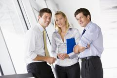 Three businesspeople standing in corridor smiling Stock Photos