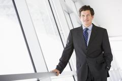 Businessman standing in corridor smiling - stock photo