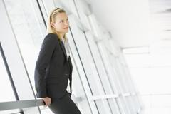 Businesswoman standing in corridor Stock Photos