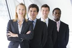Four businesspeople standing in corridor smiling Stock Photos