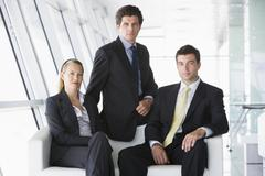 Three businesspeople sitting in office lobby Stock Photos