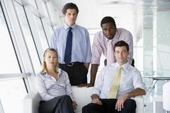 Four businesspeople in office lobby Stock Photos