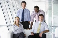 Four businesspeople in office lobby smiling Stock Photos