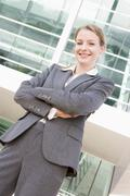 Businesswoman standing outdoors smiling - stock photo
