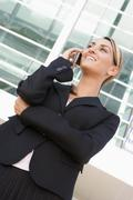 Businesswoman standing outdoors using cellular phone and smiling - stock photo