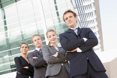 Four businesspeople standing outdoors smiling Stock Photos