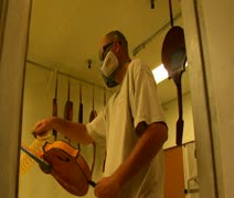 worker wearing a respirator sprays finish on mandolin - stock footage