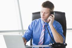 Businessman sitting in office with laptop on telephone - stock photo