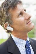 Businessman wearing headset outdoors - stock photo