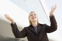 Businesswoman standing outdoors by building with hands out smiling - stock photo