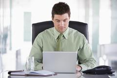 Businessman sitting in office with personal organizer and laptop - stock photo