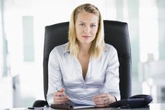 Businesswoman sitting in office with personal organizer Stock Photos