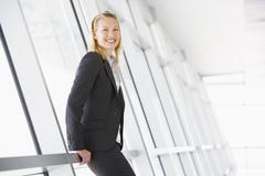 Businesswoman standing in corridor smiling Stock Photos