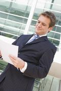 Businessman standing outdoors looking at paperwork Stock Photos