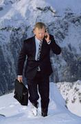 Businessman outdoors on snowy mountain using cellular phone - stock photo