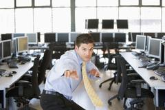 Businessman standing in karate stance in computer room Stock Photos