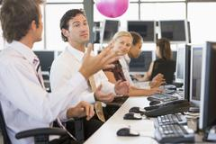 Five businesspeople in office space with a ball being thrown Stock Photos