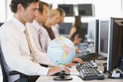 Five businesspeople in office space with a desk globe in foreground - stock photo