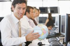 Businessman in office space with a desk globe - stock photo