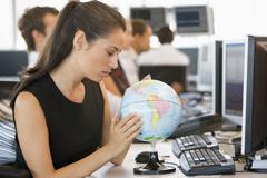 Businesswoman in office space with desk globe Stock Photos
