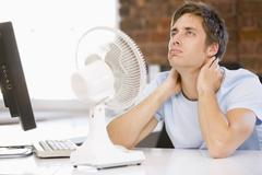 Stock Photo of Businessman in office with computer and fan cooling off
