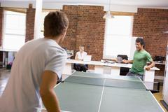 Two men in office space playing ping pong Stock Photos