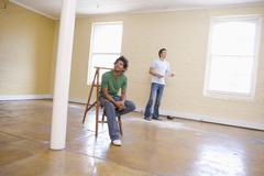 Two men in empty space with ladder holding paper Stock Photos