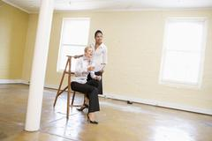 Two women in empty space with ladder holding paper and smiling - stock photo