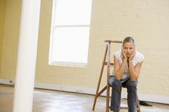 Woman sitting on ladder in empty space looking bored - stock photo