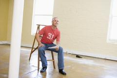 Man sitting on ladder in empty space holding paper - stock photo