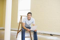 Man sitting on ladder in empty space holding paper smiling - stock photo