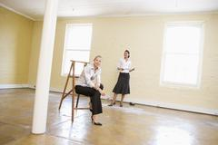 Two women with ladder in empty space holding paper smiling Stock Photos