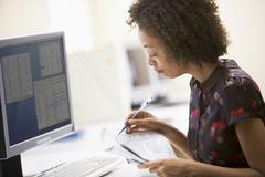 Woman in computer roon circling items in newspaper - stock photo