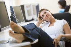 Woman in computer room with feet up thinking - stock photo