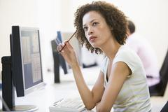 Woman in computer room thinking Stock Photos