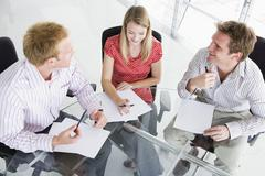 Three businesspeople in a boardroom looking at paperwork Stock Photos