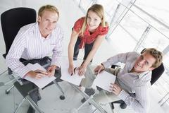 Three businesspeople in a boardroom with paperwork smiling Stock Photos