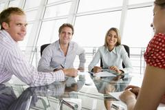 Four businesspeople in a boardroom with paperwork smiling Stock Photos