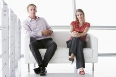 Stock Photo of Two businesspeople sitting in office lobby smiling