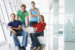 Four people in lobby smiling - stock photo