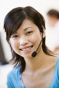 Woman wearing headset indoors smiling Stock Photos