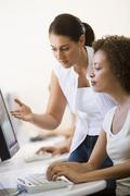 Two women in computer room where one is assisting the other Stock Photos