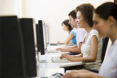 Four people in computer room typing and smiling - stock photo